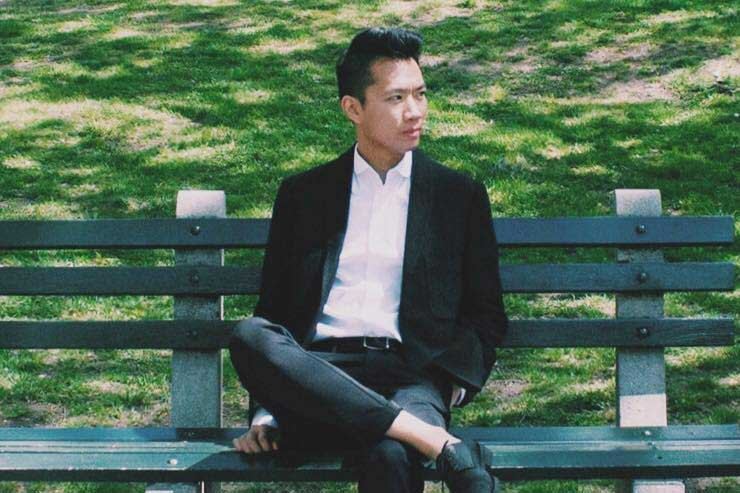 Senior Graphic Designer, Mike Nguyen relaxing on a park bench